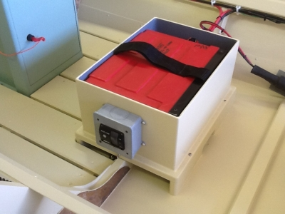 One of two battery boxes which fit beneath removable thwarts. Each house a 12V lithium ion battery wired for 24V engine operation. The small panel to one side houses the 12V automatic bilge pump panel.