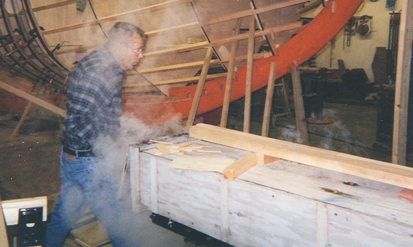 Teddy Crosby pulling steamed frame stock from the steam box. He'll rush over to where it is to be bent. He only has about 30 seconds before the frame cools too much to bend properly.